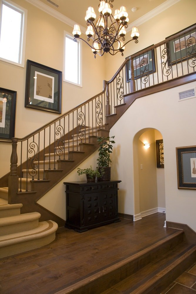 The small dark wooden cabinet at the side of the staircase stands out against the light tone of the walls and it matches well with the wrought iron chandelier hanging from the tall beige ceiling that complements the wooden elements of the staircase.