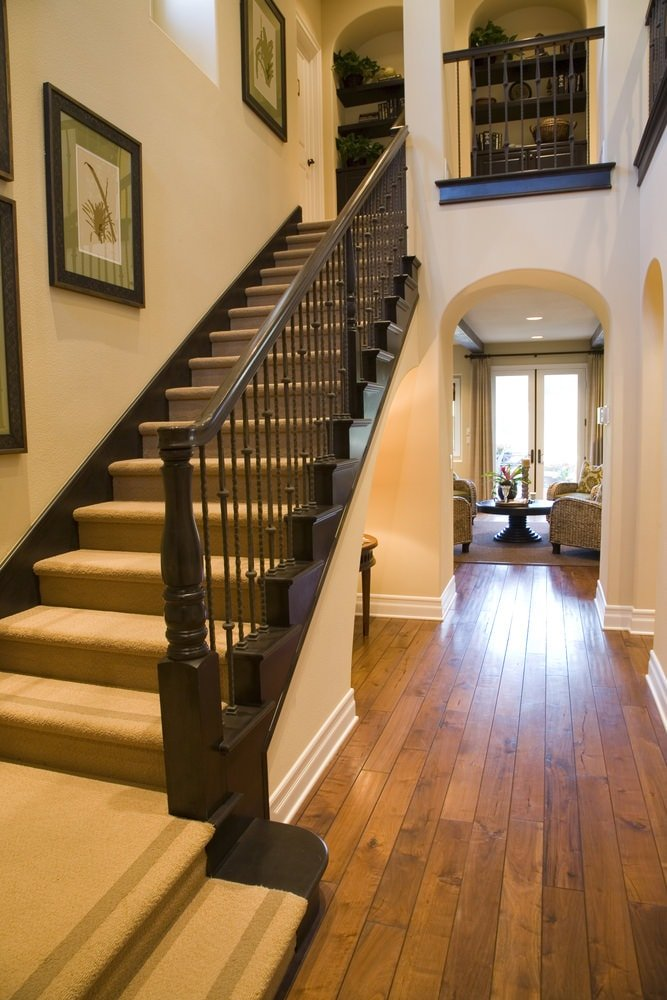This is a simple and homey foyer with a staircase right by the entry onto hardwood flooring that is complemented by the dark wooden banister of the stairs and the beige carpeted middle of the steps. These are also enhanced by the beige walls that are adorned with framed artworks.
