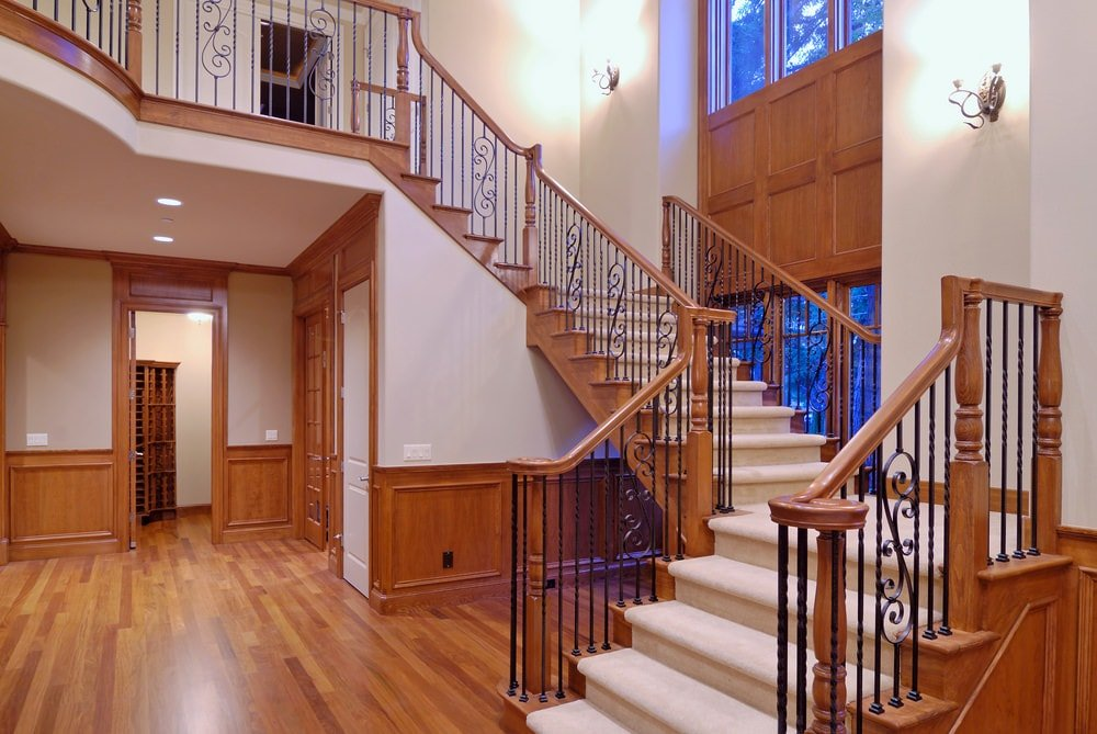 The light gray walls of this foyer is complemented by the wooden wainscoting of the same tone as the hardwood flooring and the wooden banister of the staircase that has wrought iron railings on the side and a beige carpeting that is augmented by the wall-mounted lamps.