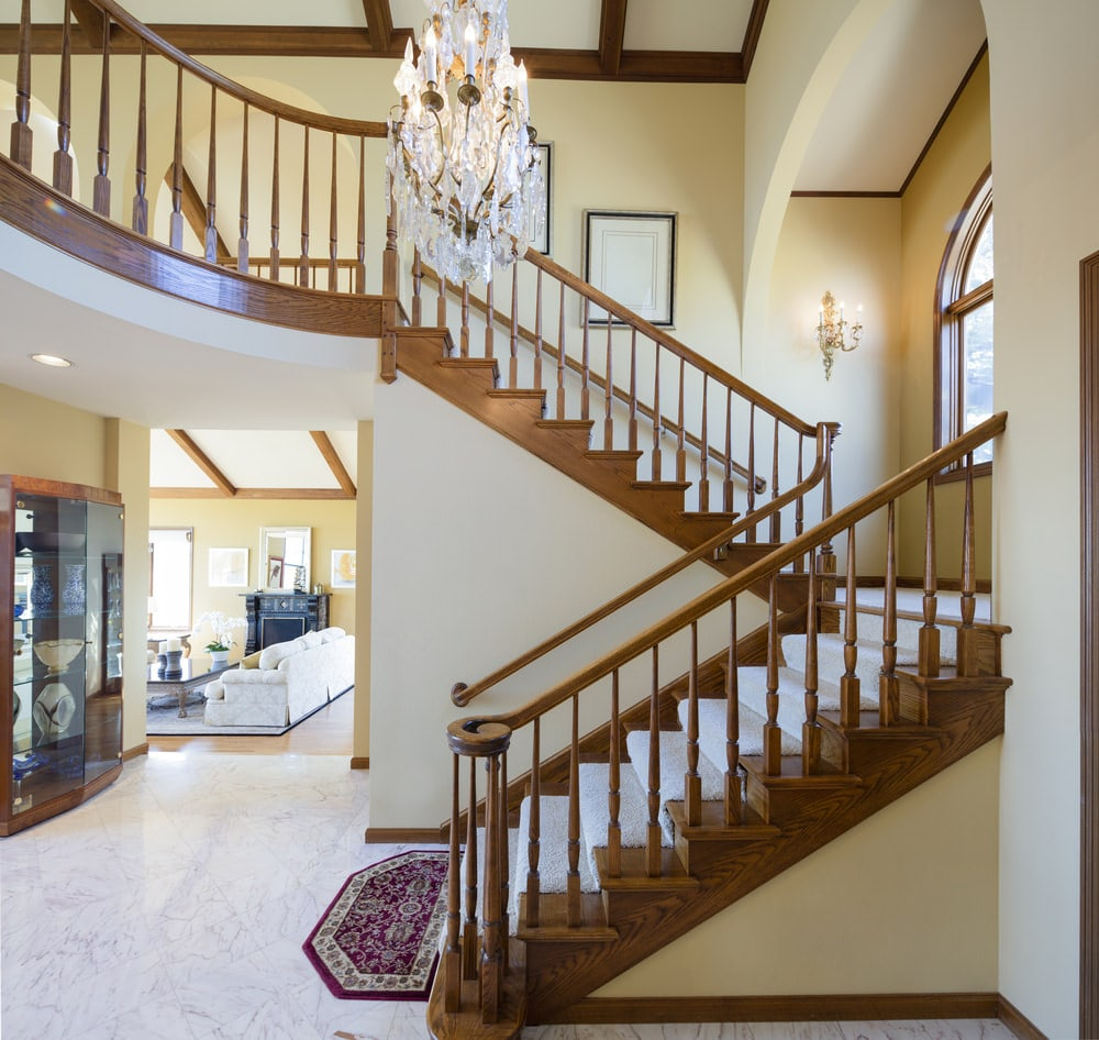 The large crystal chandelier stands out in this simple foyer that has white marble flooring and a tall ceiling with exposed wooden beams to match the wooden railings and banister of the staircase adorned with a small purple patterned area rug at the bottom.