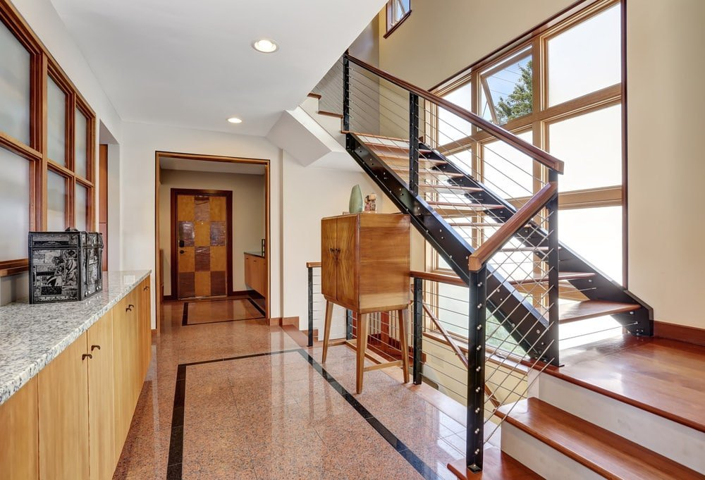 The modern staircase of this second floor landing has black metal frames and wooden steps bordered with metal wires and illuminated by the tall glass windows on its side. This also brings natural lights to the brown marble flooring outlined with black.
