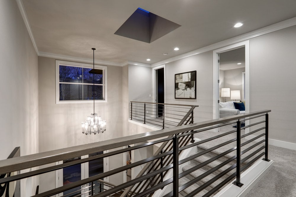 This is a modern second floor landing with light gray walls that are augmented by the black iron railings of the stairs extending to those bordering the sides of the landing. These are all brightened by the brilliant white chandelier hanging over the simple foyer.