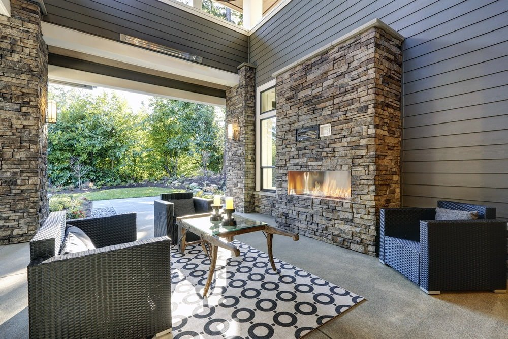 This porch has a tall wooden ceiling that matches well with the wooden exteriors and the textured stone structures, one of which houses a modern outdoor fireplace that warms those relaxing on the woven wicker armchairs paired with a patterned area rug.