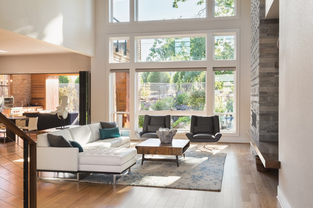 There is a large white L-shaped sectional sofa that is paired with a couple of black leather chairs to surround the wooden coffee table on the blue-green floral area rug of the hardwood flooring. These are augmented by the tall ceiling and the matching tall windows of the wall.