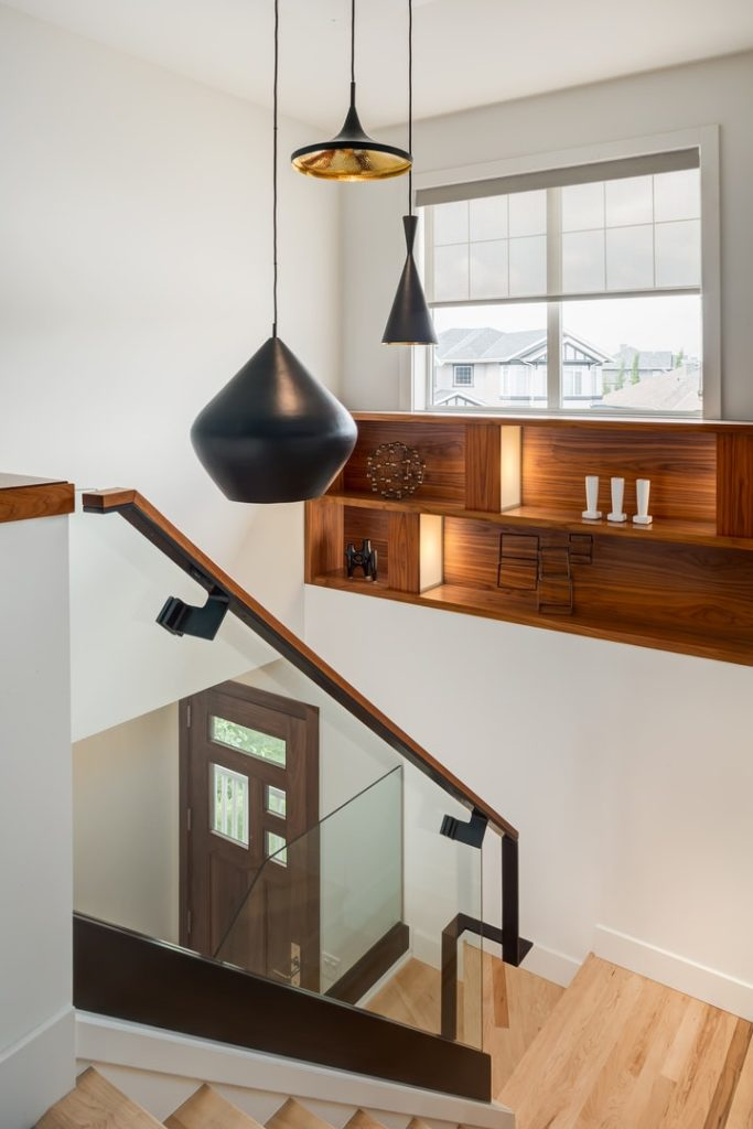 There are three pendant lights hanging from the high white ceiling with different sizes and shapes all in matte black hues that stand out against the white walls adorned with floating shelves and transom windows that brighten the tall ceiling.