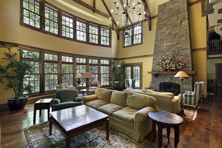 The hardwood flooring of this large living room has enough space for three living room areas. One is by the fireplace embedded into a large stone structure, the second is a simple setup with a wooden table and the last one is by the large wall of windows with a potted plant at the corner.