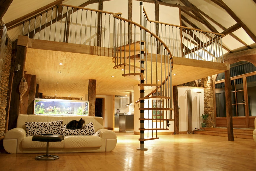This view from the ground floor that has a wide hardwood flooring allows for a look at the charming spiral staircase beside the beige leather sofa. This spiral staircase leads to the second level loft with white metal railings and a white tall cathedral ceiling that has exposed wooden beams.