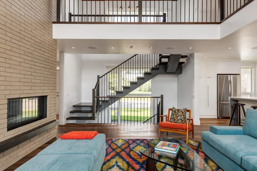 The modern glass-enclosed fireplace is embedded into a large brown bricked wall that go well with the dark hardwood flooring that is topped with a colorful patterned area rug. This also complements the two blue cushioned couches.