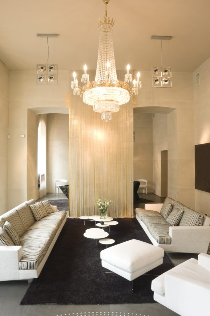 The tall beige ceiling has enough space to allow a large crystal decorative chandelier that casts yellow light. This hangs over this living room that has two white sofas and an armchair with foot stool. These surround the set of small white circular coffee tables.