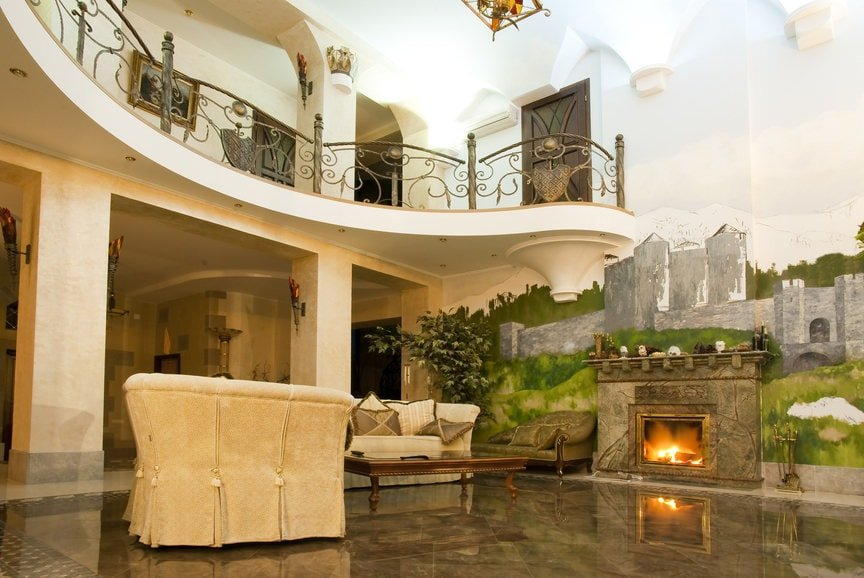 This charming and cozy living room has a fireplace with a stone mantle. This is complemented by the wall dominated by a gorgeous mural of an ancient castle and the scenery that comes along with it. It reaches up to the tall white ceiling with arches on the upper walls.