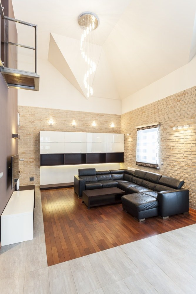 The tall beige ceiling hangs a set of decorative pendant lights over the black leather L-shaped sectional sofa and its dark brown wooden coffee table that blends with the dark hardwood flooring. This works well with the textured brick walls.