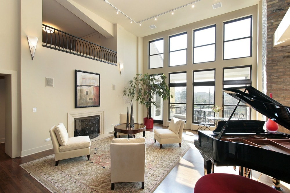 The row of glass transom windows above the glass wall and glass door of the ground floor brings in an abundance of natural lighting to the beige cushioned chairs that blend well with the beige walls that has a fireplace embedded into it beneath the painting.