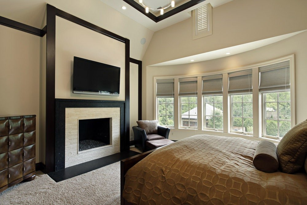 The fireplace and TV are both houses by a large beige panel of the wall that has dark moldings matching the moldings of the tall beige ceiling. This setup is paired with a wooden bed that has a brown patterned sheet and a reading area by the row of windows.