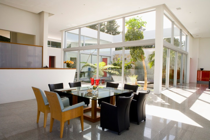The tall glass walls of this dining area showcase the tall trees and tropical plants just outside at the backyard. This gives a colorful and complex contrast to the white flooring, white walls, dining set and white tall ceiling with recessed lights.