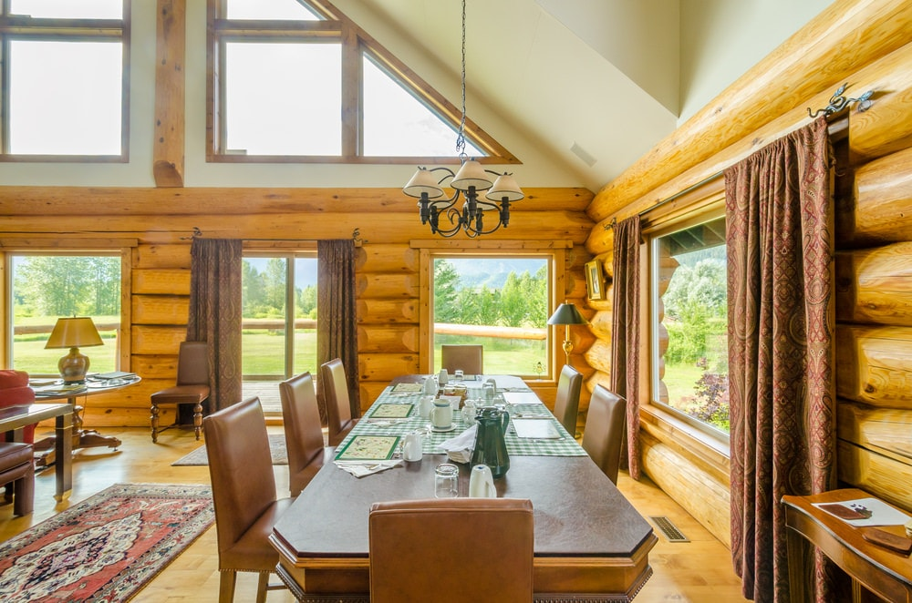 This charming dining area has log beam walls that match perfectly with the wooden ceiling. This tall ceiling has a cathedral design that is paired with a couple of triangular transom windows to follow the lay of the ceiling that hangs a chandelier over the wooden table.