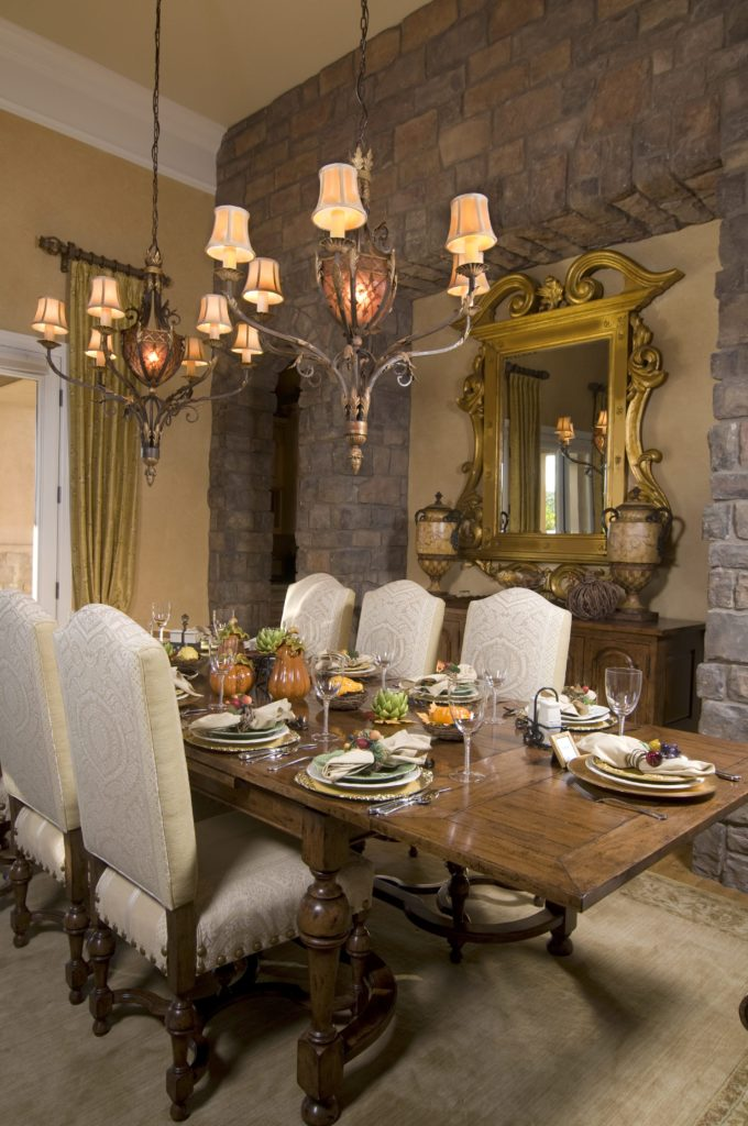There is a textured gray stone wall beside the wooden dining set. This wall has alcoves adorned with a golden mirror mounted above the wooden dining room cabinet. This mirror matches with the design of the wrought iron chandeliers hanging from a tall ceiling.