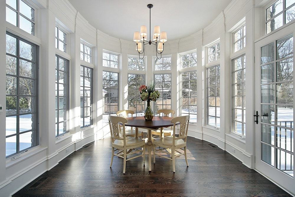This is a simple dining room that is brightened by the surrounding tall windows of the curved wall reaching up to a tall ceiling that hangs a simple chandelier over the round wooden dining table surrounded by beige wooden dining chairs.
