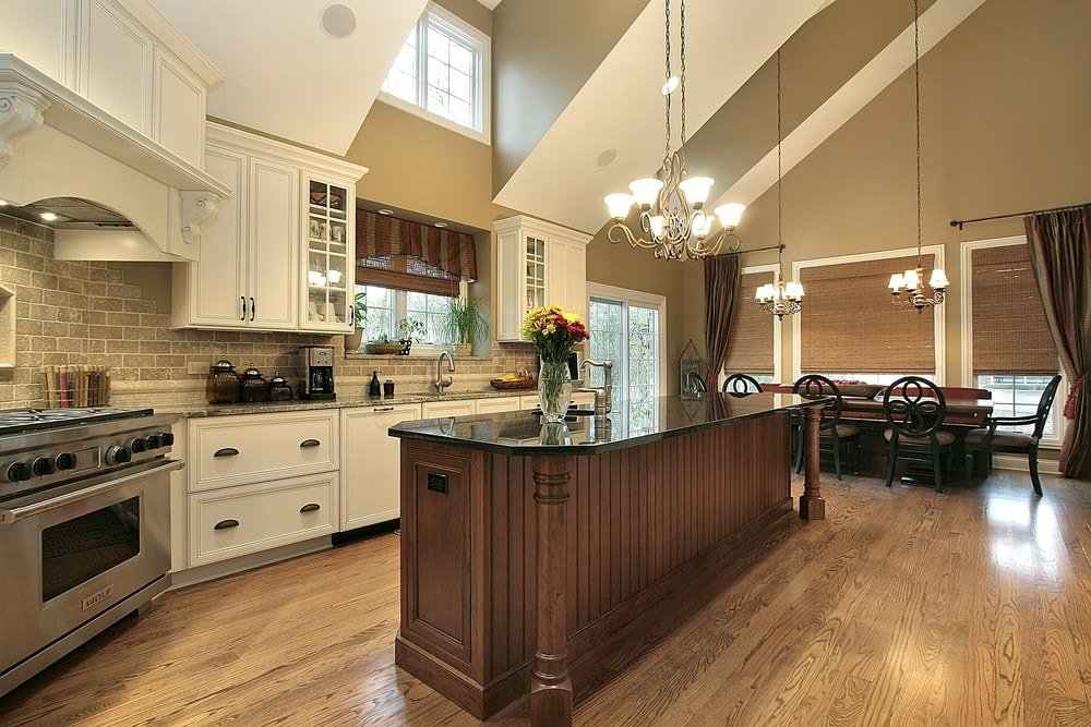 The dark brown wooden kitchen island matches well with hardwood flooring but contrasts the white shaker cabinets and drawers of the peninsula that has floating cabinets near the white arches of the tall ceiling with a single transom window in the middle.