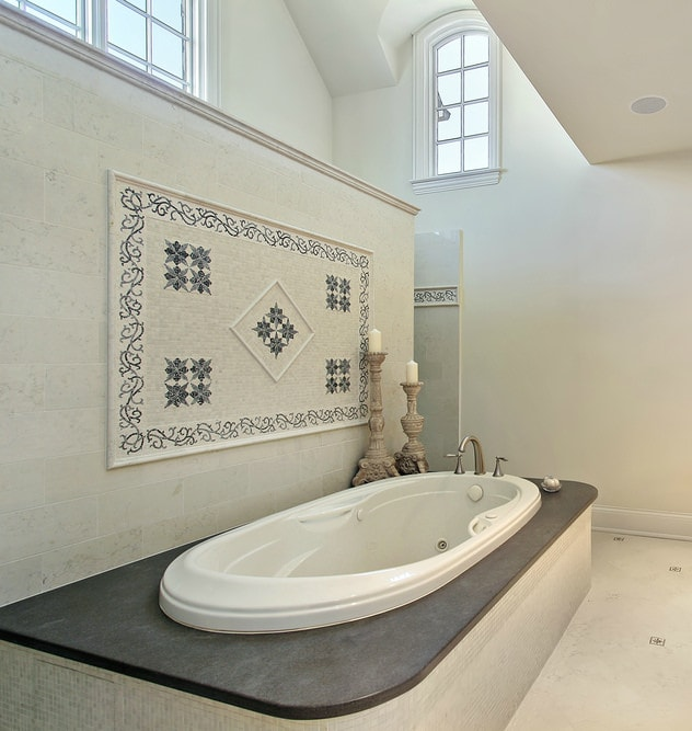 This is an elegant bathroom with a white porcelain bathtub housed within a dark countertop and beige tiles with a decoration on the side with complex patterns. This is topped with a tall arched ceiling that is brightened by the arched transom windows.