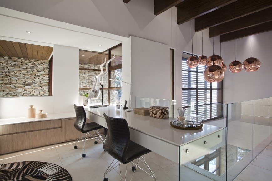 This modern and luxurious home office has a white modern desk that contrasts the black leather chairs facing the high ceiling area of the second floor landing. This tall ceiling is dominated by its exposed wooden beams and hangs several decorative spherical pendant lights.