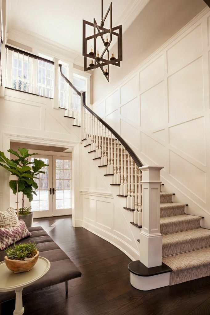 The light wooden hue of the elegant walls are contrasted by the dark hardwood flooring of this bright foyer. This foyer has a brown cushioned bench on the side that blends with the floor that is adorned with a potted plant and a smaller one by the stairs.
