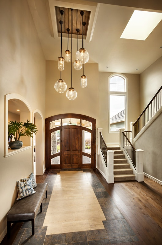 The large wooden arched door is the highlight of this spacious foyer. It has a couple of side lights that has glass panels to bring in natural lighting to the dark flooring tiles that look like wood. There is a brown leather cushioned bench on the side that matches this hue.