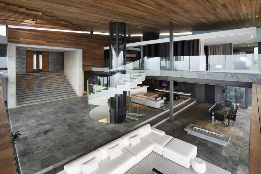 This is a massive great room with a wide open gray marble flooring and a wide wooden tall ceiling. This houses the living room, dining room and entertainment area all in one room. In the middle of this is a large spiral staircase walled within a glass tube.