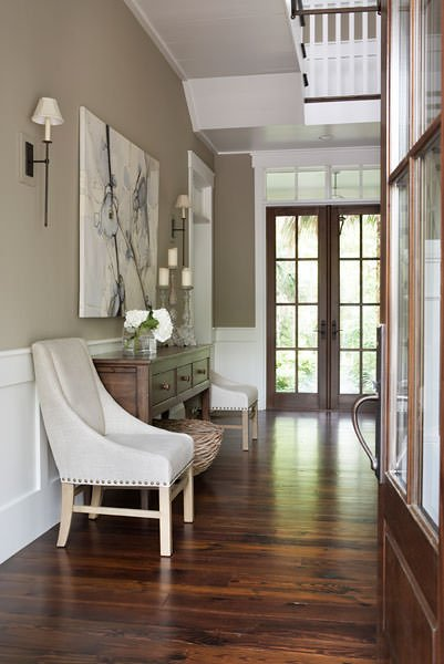 The dark hardwood flooring of this simple and welcoming foyer matches well with the dark wooden main door that has glass panels. The flooring is contrasted by the wooden white wainscoting that matches the white ceiling and the white wooden railings of the second floor landing.