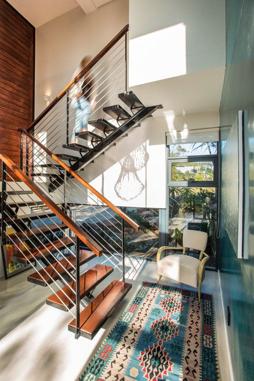 The simple modern staircase that has black iron frames and support is fitted with wire railings on its sides topped with wooden banisters that match the wooden steps. This is augmented by the colorful patterned area rug at the bottom and the tall brick wall.