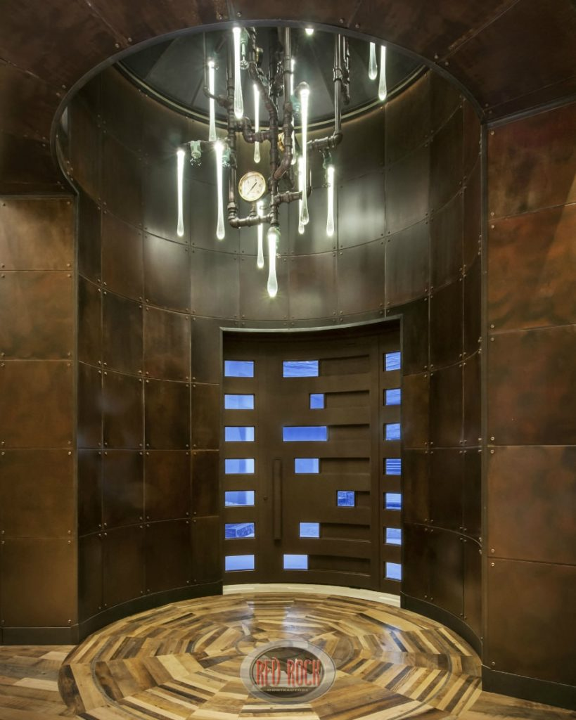 This Industrial-style foyer has an awesome theme to its walls of brass, tall metallic ceiling and the highlight of the foyer which is the steam-punk decorative chandelier made of water pipes fitted with light bulbs that look like melted glass.