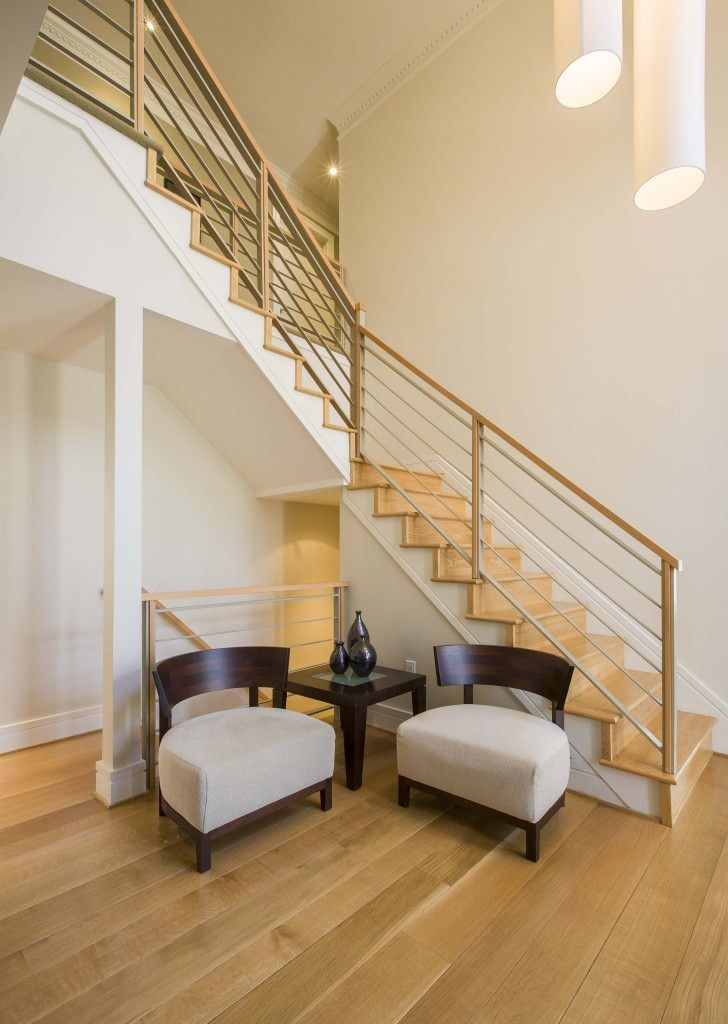 This simple and charming second floor landing is complemented by the light wooden tones of the light hardwood flooring, stairs and the railings of the stairs to the next floor. This is augmented by a tall ceiling that hangs decorative lighting over the area.