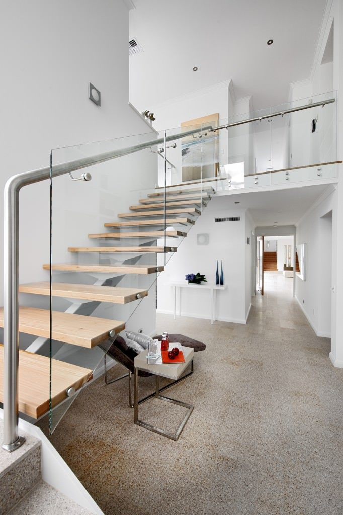 This foyer has a modern staircase that is bordered with glass and framed with metal beams extending to the second floor landing. This goes well with the white and bright walls that extend to the tall ceiling two floors above from the ground level.