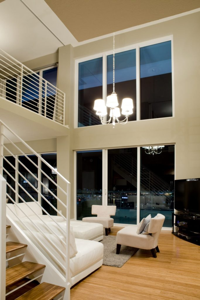 This living room is placed by the staircase that has its white railings extend to the second floor loft that looks over the living room. This living room has a matching white leather sofa and a couple of cushioned wing-back chairs that stand out against the tinted glass walls reaching up to the tall ceiling.