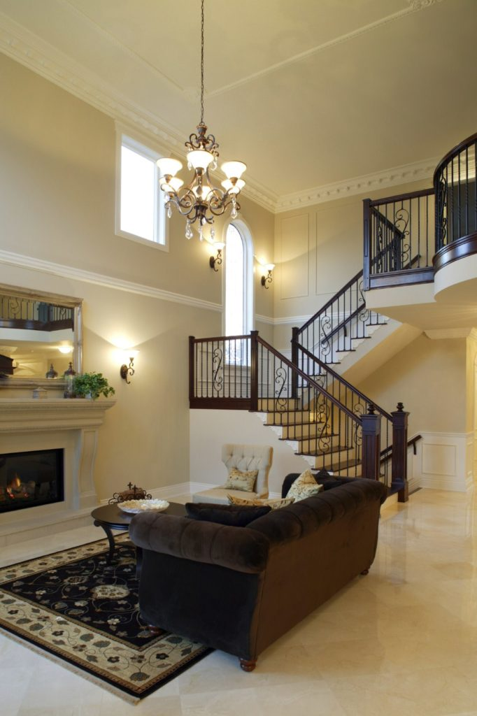 The consistent light beige tone of the tall ceiling, walls and the beige marble flooring is contrasted by the dark velvet sofa and the dark railings of the staircase leading to the second floor landing that is the same level as the hanging wrought iron chandelier.