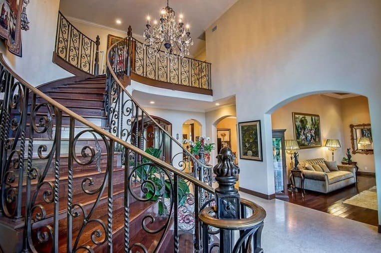 The elegance of this grand foyer stems from the majestic chandelier that matches with the wrought iron railings of the curved staircase. This staircase has wooden steps matching the hardwood flooring of the living room through the arched entryway on the side.
