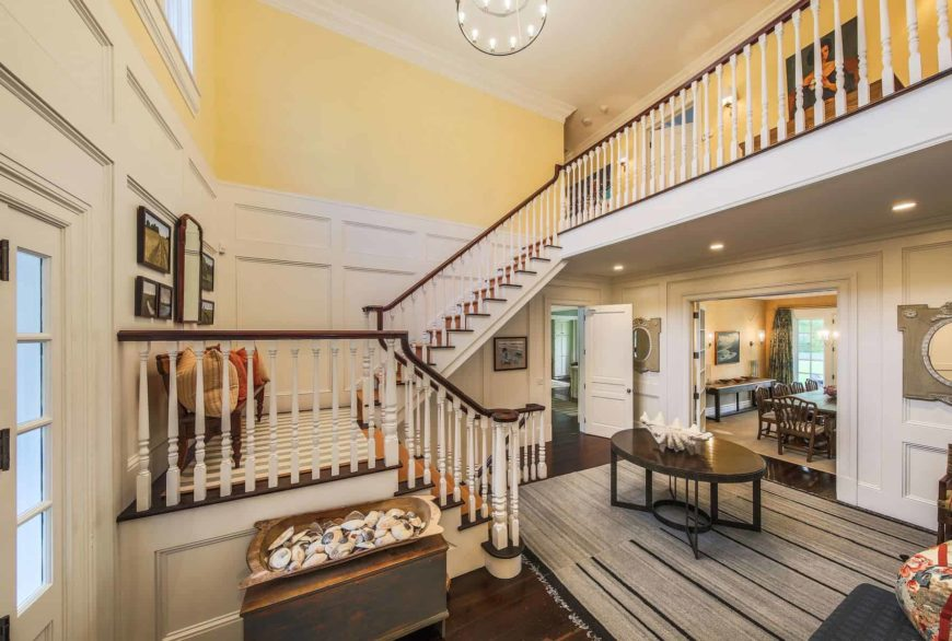 This foyer provides a charming welcome for the guests with its high and white ceiling illuminated by a round chandelier with complementing white lights for the cheerful yellow walls complemented by the white wainscoting and the white wooden railings.