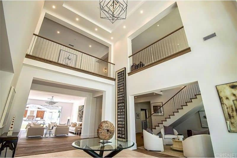 This immense foyer has a tinge of modern sensibility to its traditional high white ceiling and white walls. This is complemented by the large decorative metal pendant light hanging over the round glass-top table in the middle of the entryways to different sections of the house.