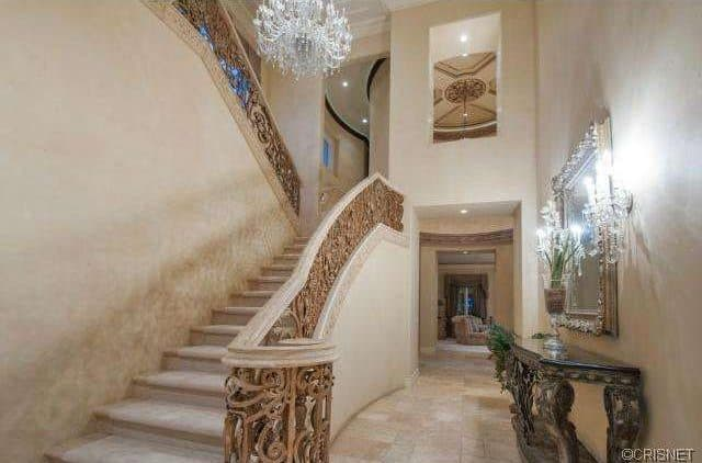 This is an ultra elegant foyer with staircase railings made of complex patterns in a brown hue that matches with the earthy beige tone of the walls and the stairs. These are augmented by the brilliant white and crystal chandelier that matches with the wall lamps above the wooden console table.