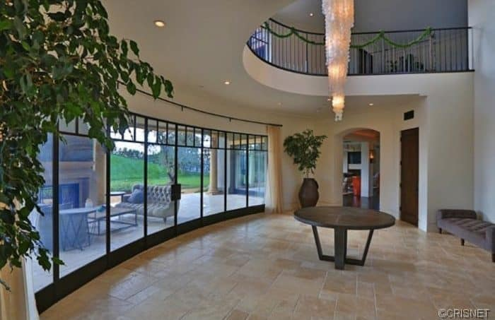 The middle part of the foyer's ceiling opens up to let the large decorative lighting come down toward the circular dark table in the middle of the beige marble flooring. This area is illuminated by the large wall of tinted glass leading to the backyard.