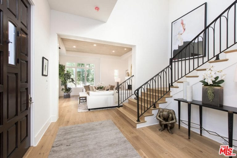 The bright white walls and tall ceiling of this simple foyer is elevated by the eclectic decoration beside the dark wooden console table. This dark table matches with the black wrought iron railings of the stairs that is adorned with a large painting.