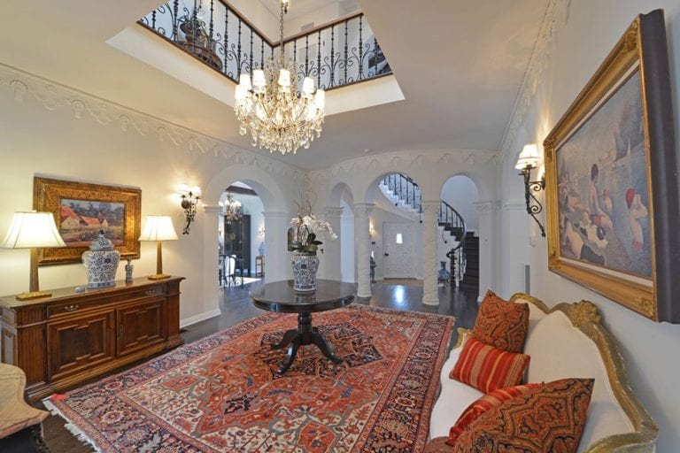 This is an elegant and luxurious foyer with a white cushioned sofa on the side for the waiting guests. This is paired with a large red patterned area rug underneath the black round table. This is topped with a chandelier hanging from the tall ceiling in the middle.