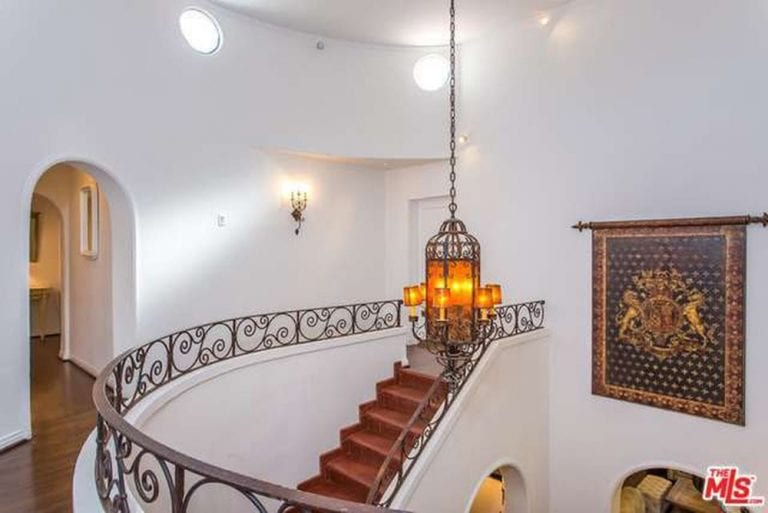 The tall white ceiling of this area hangs a charming decorative lantern pendant light that has an amber tone to it. This makes it stand out against the white walls that is adorned with a large tapestry banner beside the staircase that has terracotta steps.