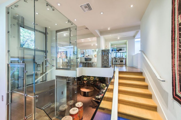 This is a super luxurious home with its own private elevator covered in a stylish glass box. This extends from the ground floor below to the tall white ceiling above that pairs well with the recessed lights and white walls that complement the hardwood flooring the same as the wooden steps of the staircase.