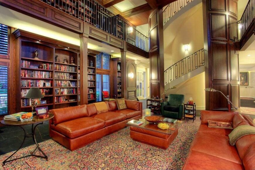 This cozy home library has a couple of large brown leather sofas augmented by the large colorful patterned area rug. These elements serve to elevate the elegance of the brown wooden book shelves that match the dark wooden walls and tall ceiling.