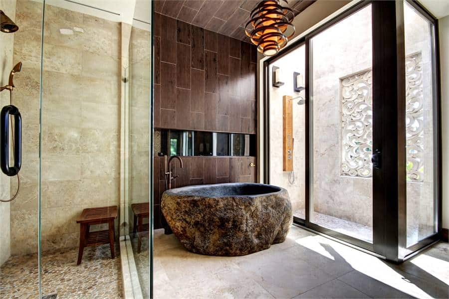 This primary bathroom is equipped with a stunning decorative light fixture and a marvelous deep soaking tub that has an earthy textured exterior flanked by walk-in showers.