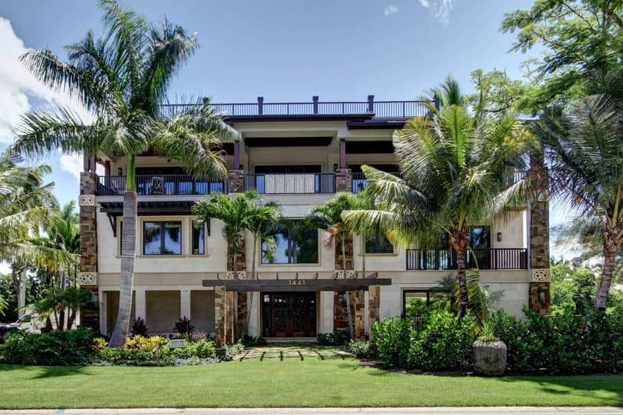 The main entrance of this house is wonderfully framed by the lush green lawn of grass as well as the tall tropical trees on both sides along with shrubs.