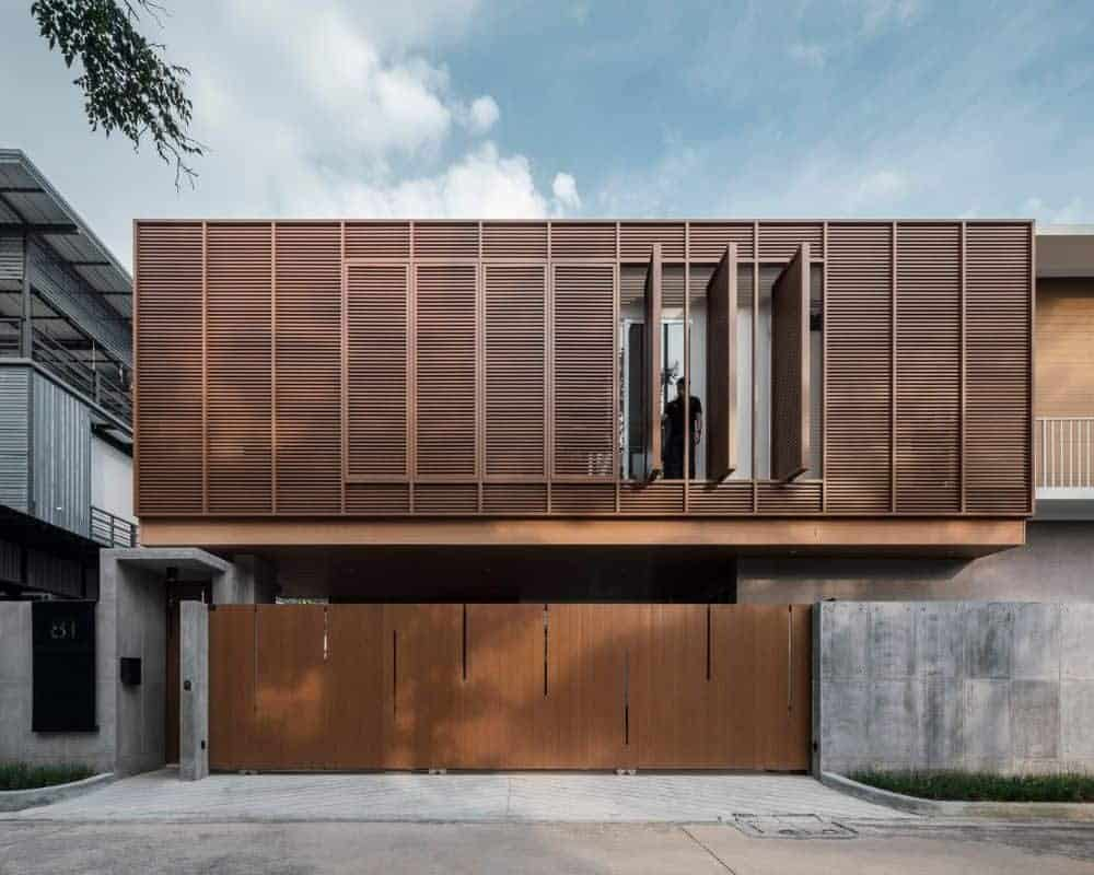 This is a front exterior of the house that has consistent dark wooden tones on the garage doors at the ground level and the slatted panels of the upper levels that has a few panels that can swivel to open the interiors.