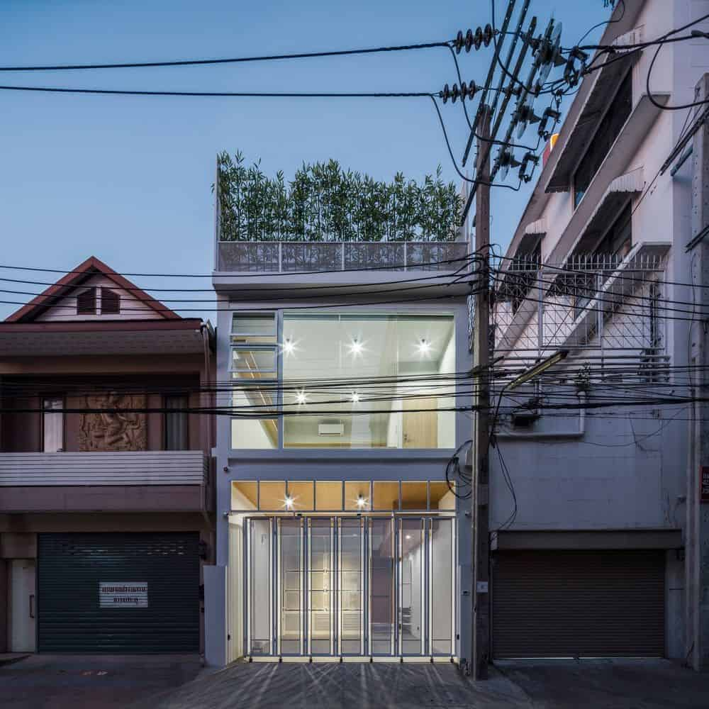 This is a nighttime view of the house exterior showcasing the opaque gate of the ground level and the glass wall of the upper level that give a glimpse of the indoor complemented by the row of bamboo plants on the rooftop level.