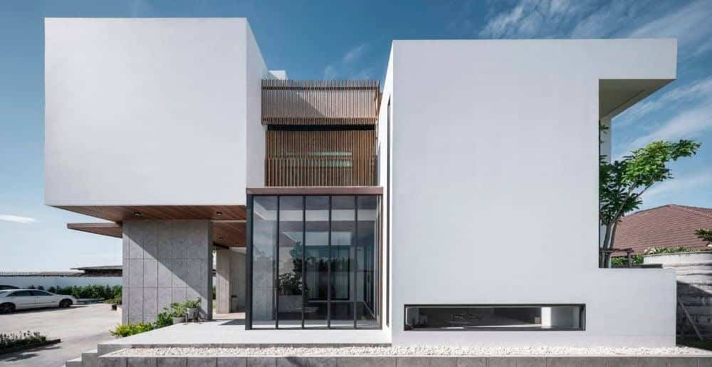 This is a front view of the house with white exterior walls with blocks and glass walls that make the wooden slatted panels of the upper level stand out.