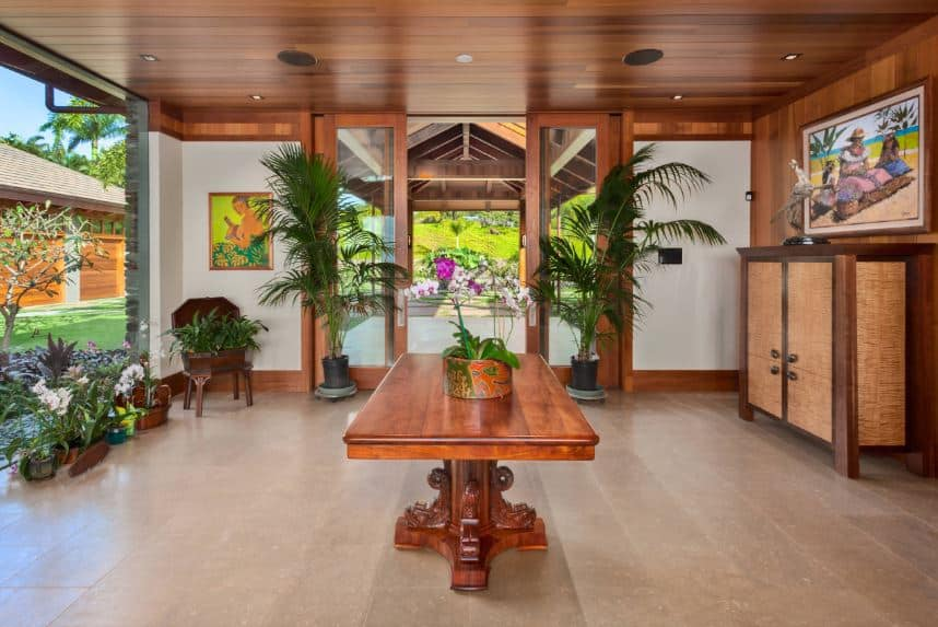 The large redwood table in the middle of the beige flooring of this Tropical-style foyer matches with the wooden tones of the ceiling and door frames. The brightness of this foyer comes from the large glass wall on the left that works well with the various potted tropical plants inside.